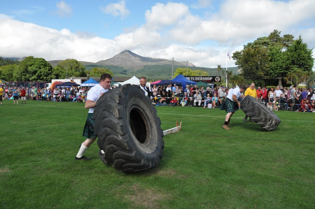 Entrants compete in the tyre flip heat of the Strongman competition.