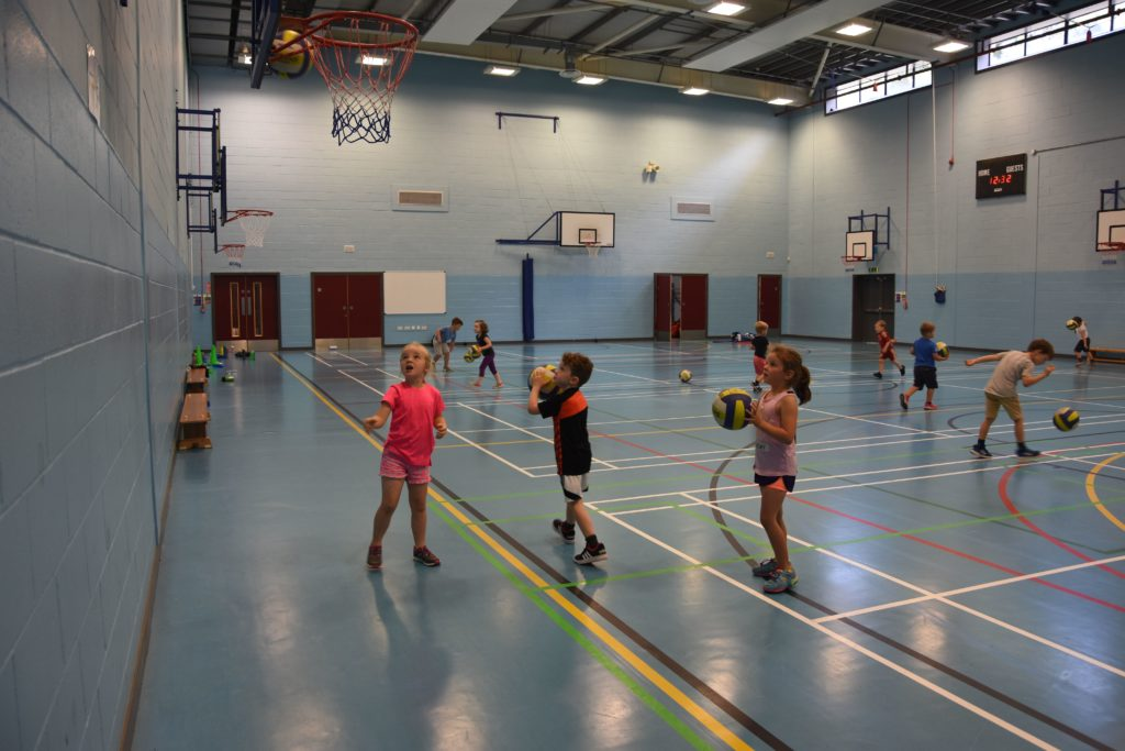 Young basketball players practice their aiming skills.