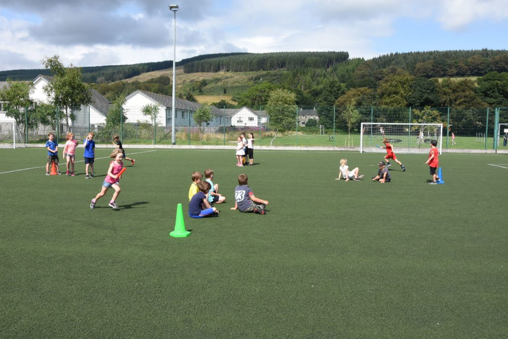 Out in the summer sunshine, children take part in a team relay race.