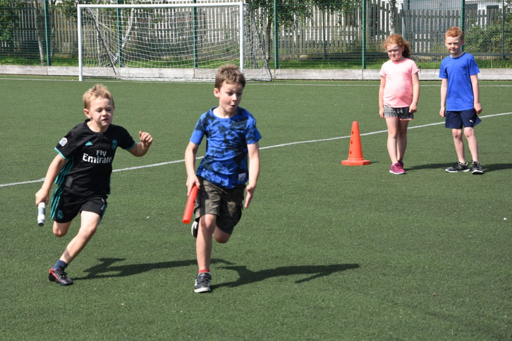 Two young boys race to the finish line in a sprint finish.
