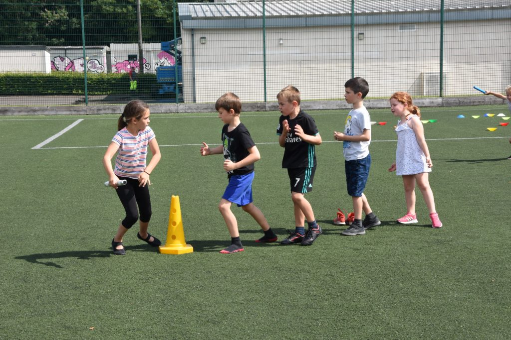 Team spirit, children cheer on their runner who sets off with the relay baton.