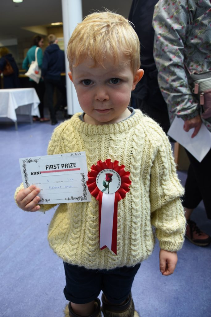 Little winner Robert Dick with his first prize rosette for his bouquet of leaves and grasses in the six years and under category.