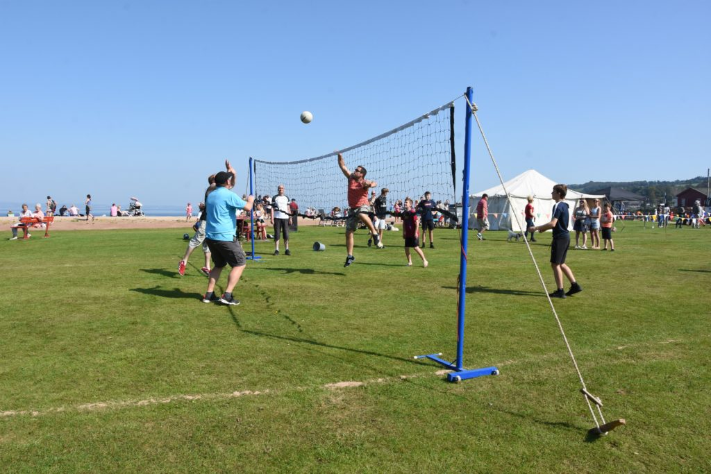 Volleyball players enjoy the physical exertions of a match on the grass.