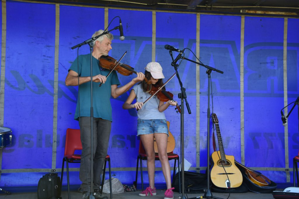 Arran Fiddle Club tutor Alistair Paul supports Kayleigh Easton in her performance on the main stage.