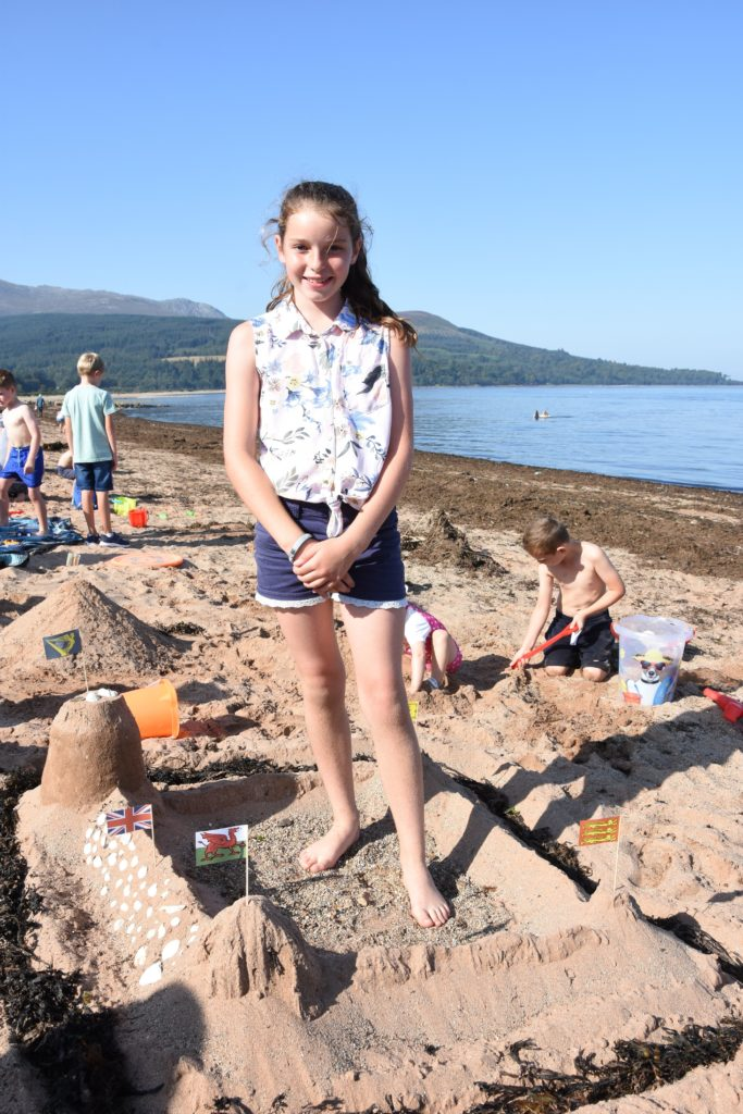 Kirsty Hume stands in the middle of her impressive sandcastle.