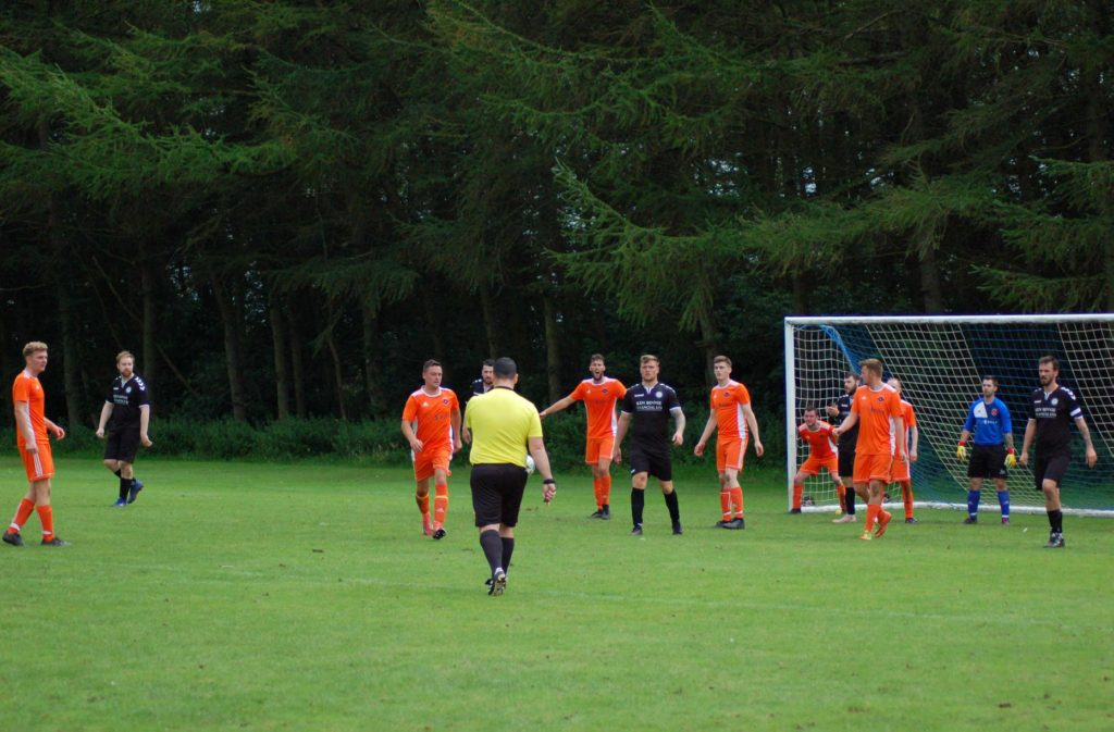 The referee awards Grange a penalty for an Arran handball committed inside the box.