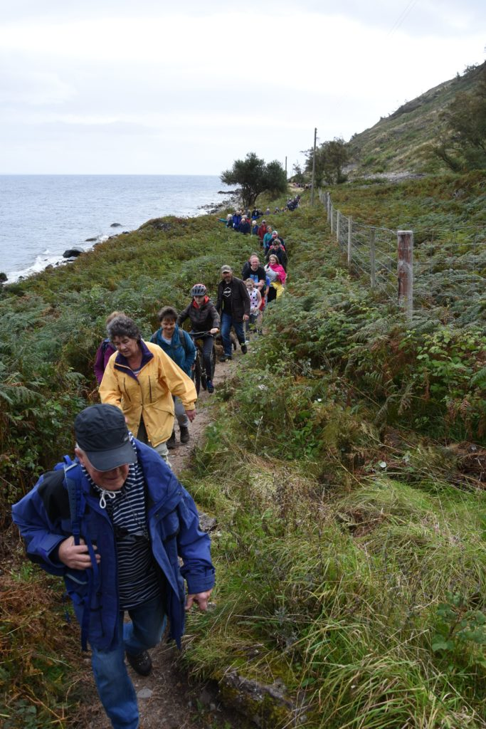 A long line of protestors make their way along the coastal path towards Millstone Point.