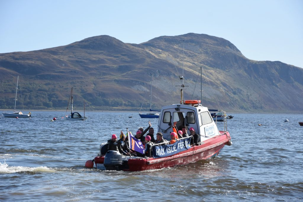 Swimmers wave goodbye as they are transported to the start of the race by the Holy Isle ferry.