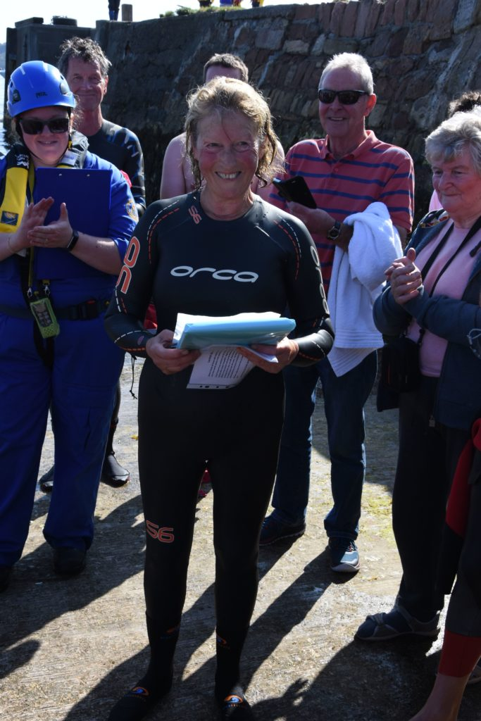 Organiser Ann Hart is presented with a gift for all of her hard work on the anniversary of her 10th swim.