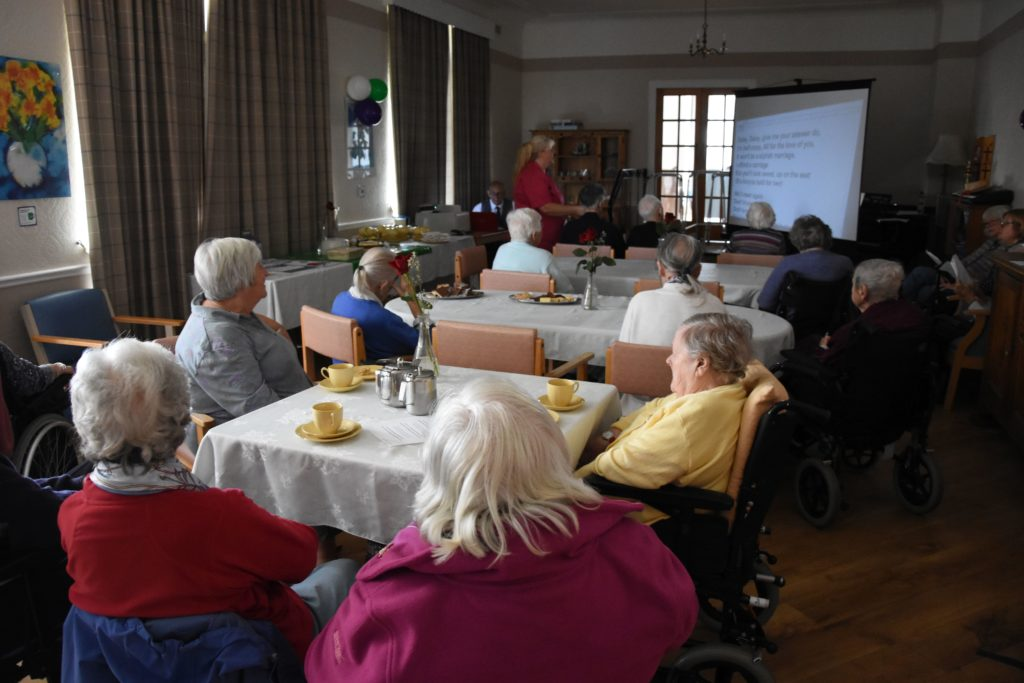 Jill McKillop leads the singing while residents and visitors enjoy their afternoon tea at Cooriedoon.