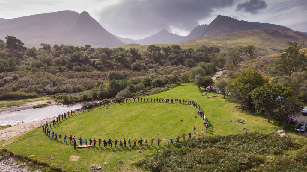 Protestors join hands to demonstrate the size of a single 120m in circumference fish pen. Photograph: James Appleton.
