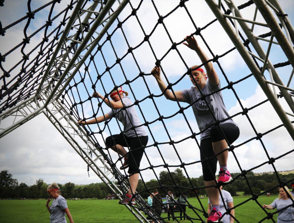 Two aspiring ninjas make light work of the climbing net obstacle.