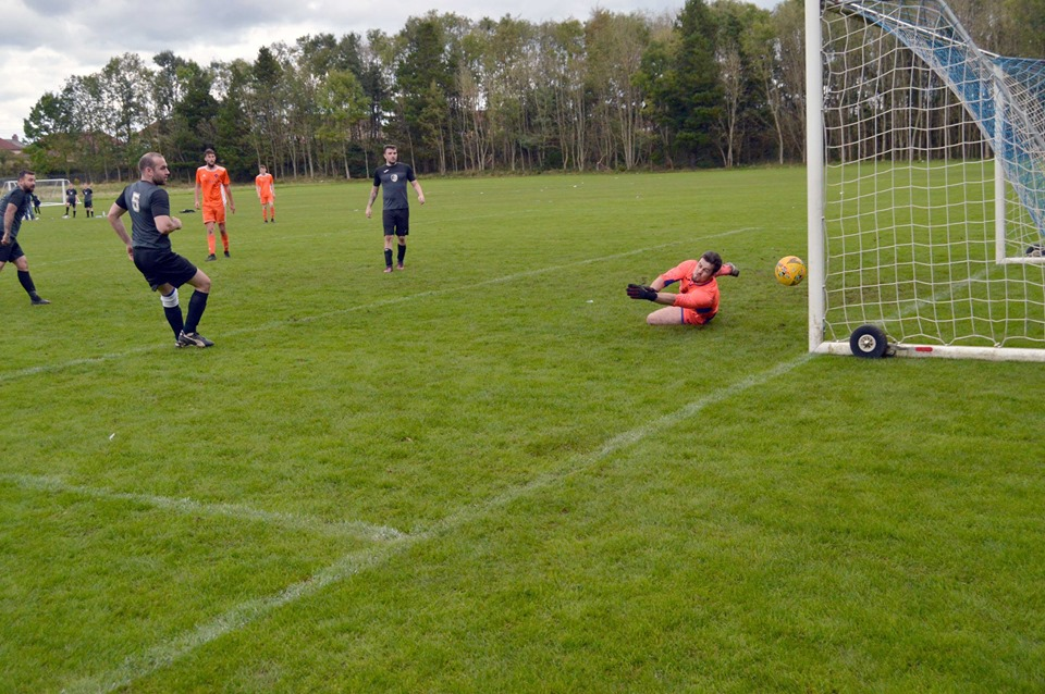 The Irvine SB keeper looks on helplessly as another ball makes it past him.