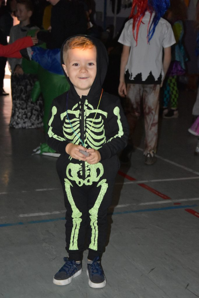 A young skeleton boy shows off his glow in the dark outfit.