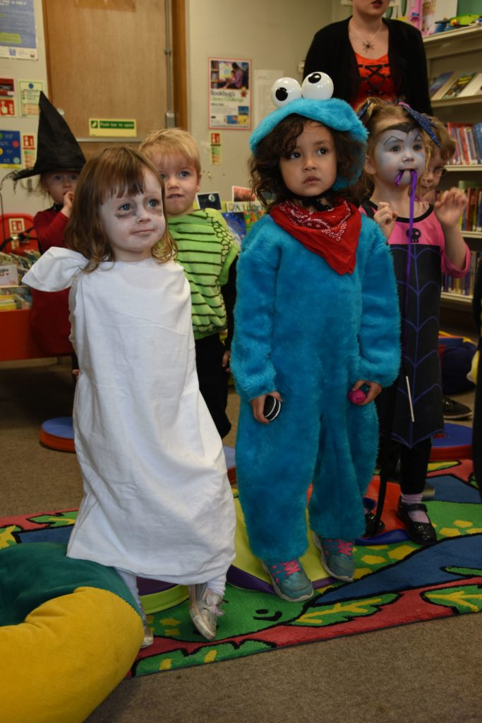 A little ghost and a Cookie Monster enjoy a dance at Brodick Nursery.