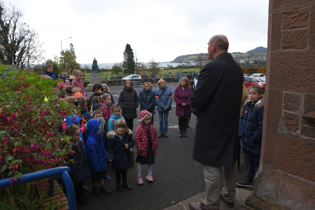 Rev Angus Adamson rededicates the memorial plaque with all of the teachers and pupils in attendance.
