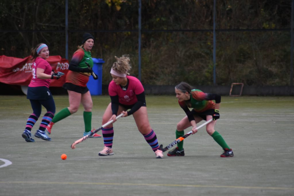 Centre back Ellie Wood secures the ball from a challenging opposition player.