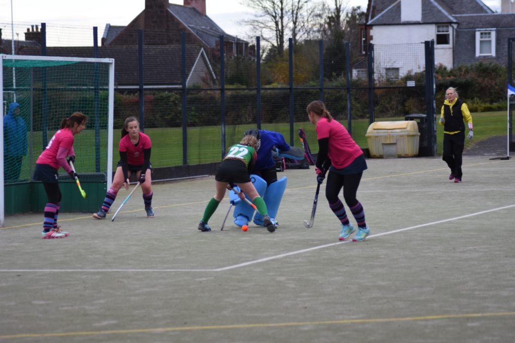 Ali 'Ninja' McKie defuses a tense moment in goal with sweeper Faith McKelvie at the ready to eject the ball from the 'D'.