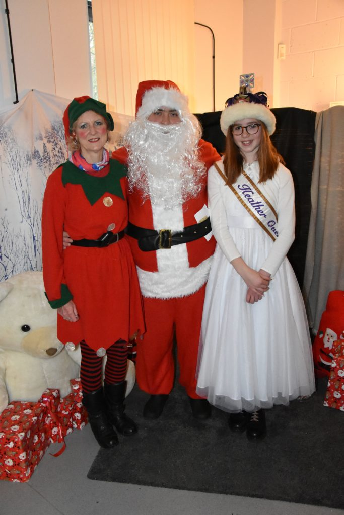 Santa (Lukasz Switek) is joined by his elf helper (Cecilia Paul) and the Heather Queen, Imogen Allison.
