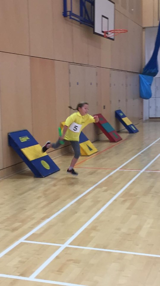 A young girl bounces off a backboard in the relay race.