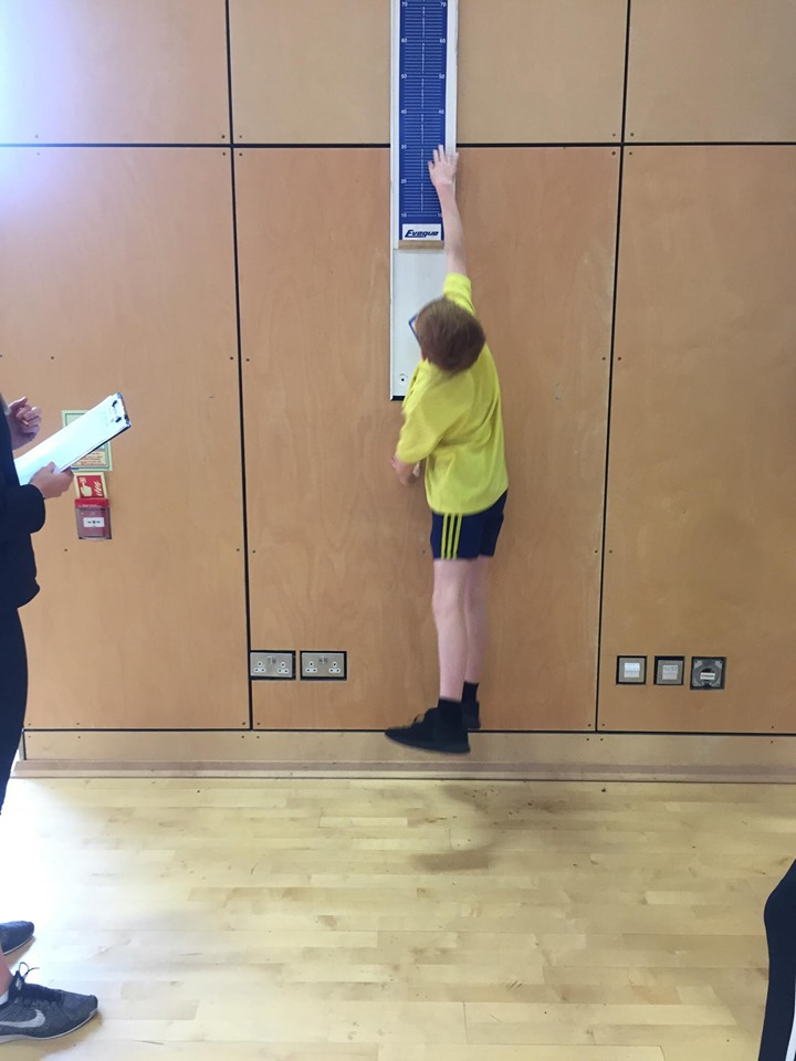 Reaching for the stars, a young boy competes in the jumping for height event.
