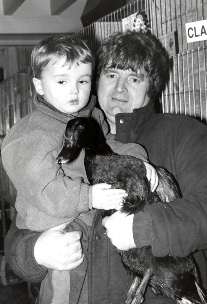 Colin Currie holds son Wallace and wife Laura's Champion Bird of the Show, a Cayuga Drake, at the Arran Chookie Show.