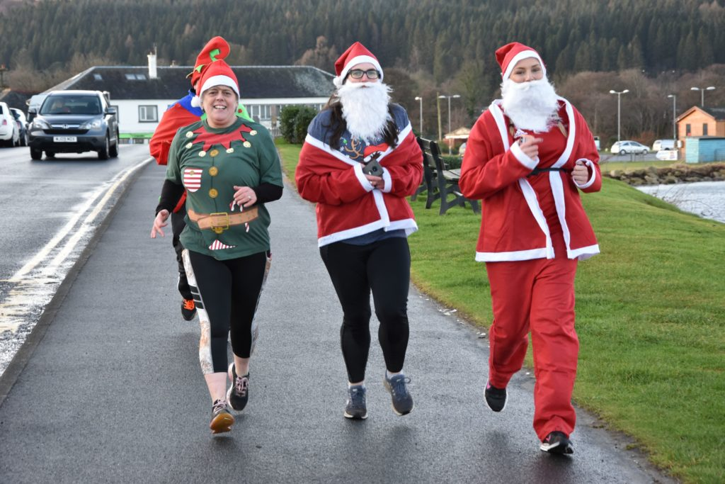 Still smiling, runners make their way along Brodick Main Road.