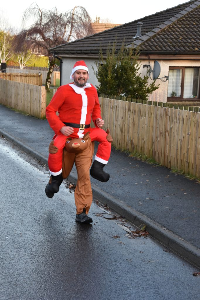 Bringing smiles to spectators' faces, Santa appears to be carried aloft by one of his reindeer.