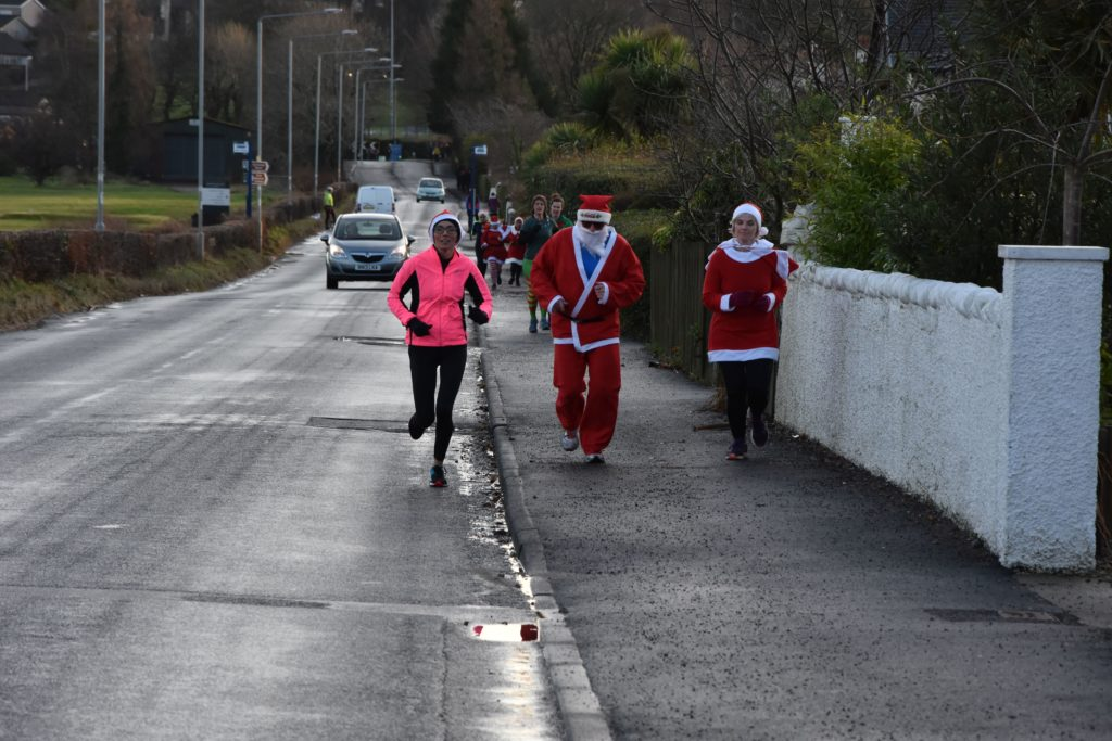 Runners make their way along the road with motorists waving and offering their support.