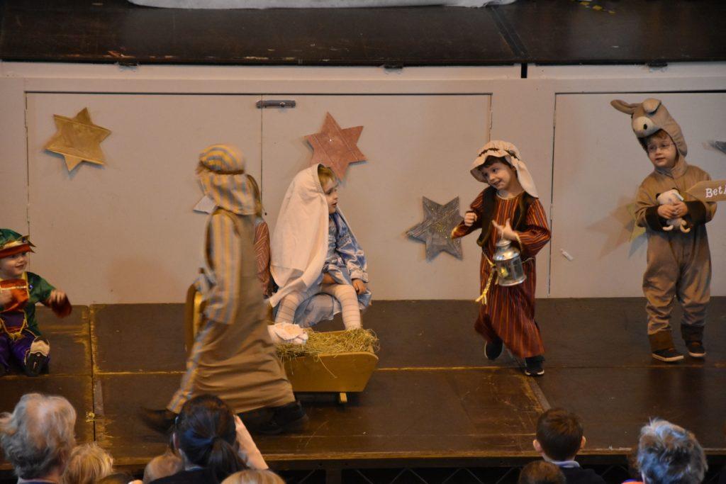 Two shepherds dance around Mary and Joseph.