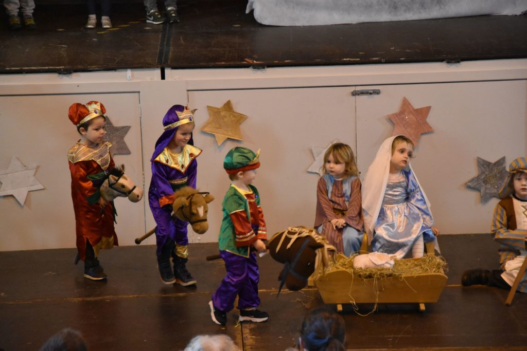 Three wise men arrive on their horses to present gifts to Mary.