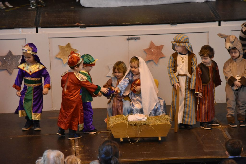 Mary and Joseph receive the offerings from the three wise men.