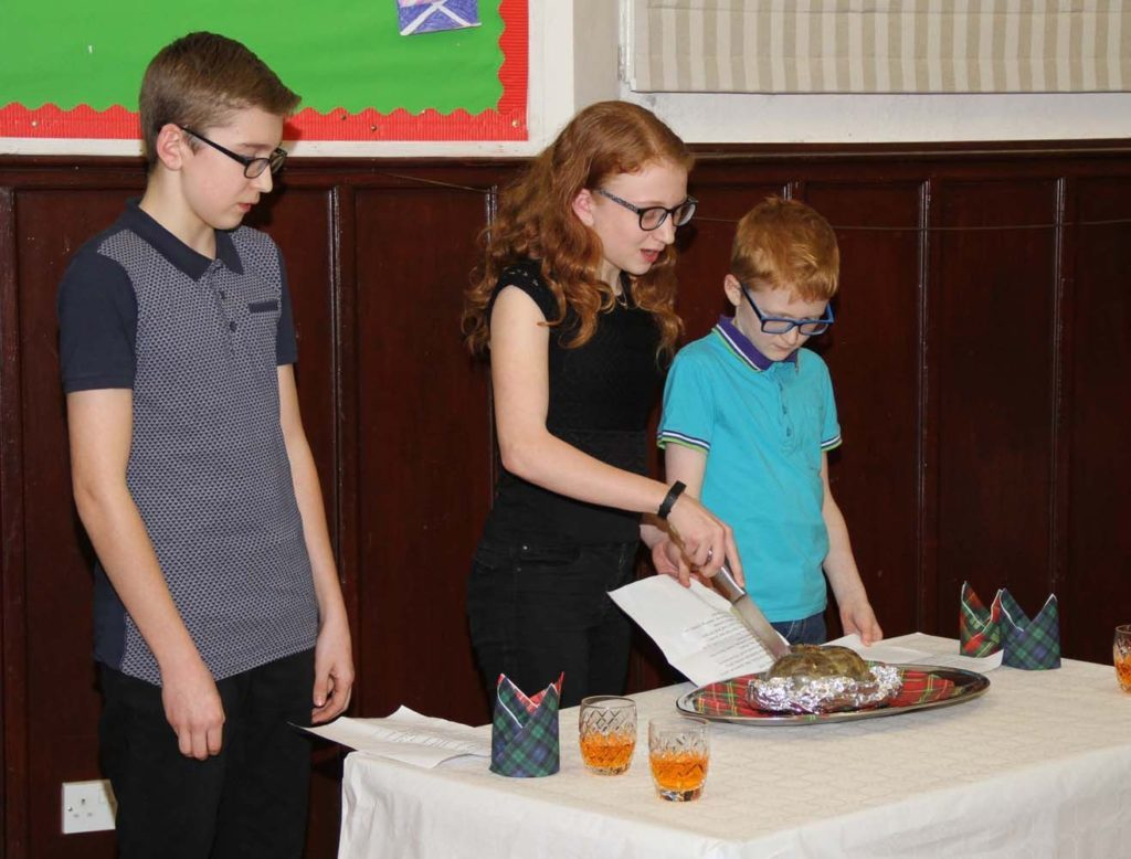 JANUARY. The McCarthy children comprising Ben, Beth and James, address the haggis at the Shiskine Burns Supper which is held every two years. Photo: Stephen Garraway.