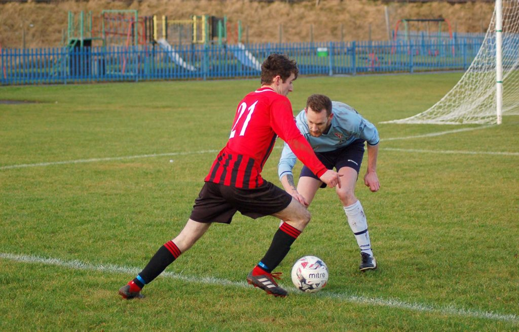 Goal scorer Johnny Sloss outsmarts an opposition player with his deceptive footwork.