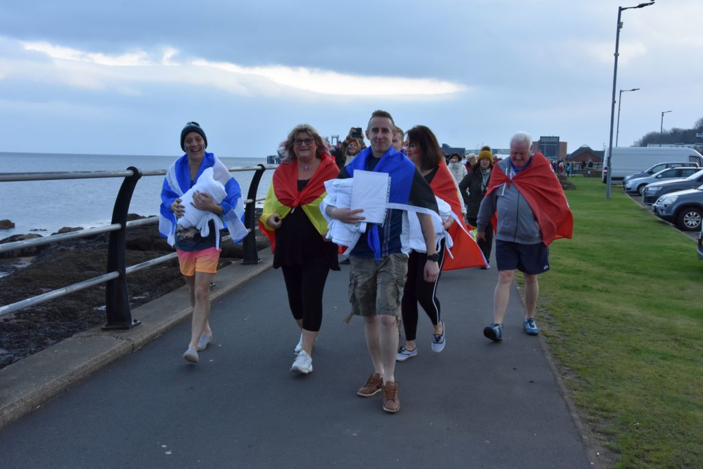Douglas Hotel staff lead the procession from the hotel to the Brodick slipway.