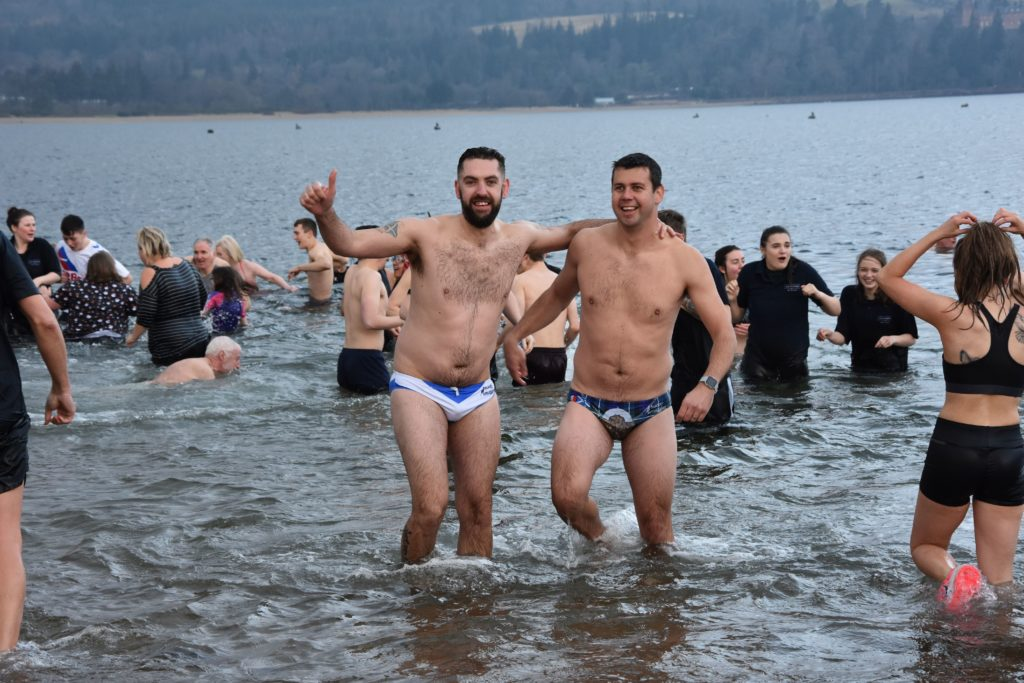 Two swimmers with little to keep them warm smile for the camera.