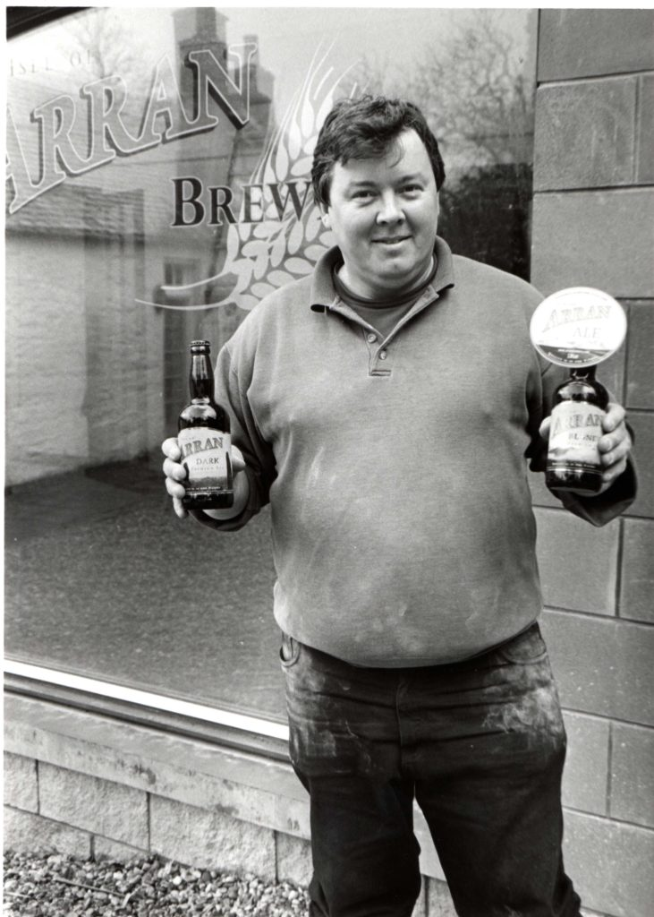 Richard Roberts outside his new brewery holding bottles which will soon contain his Arran Ale and Arran Blonde.