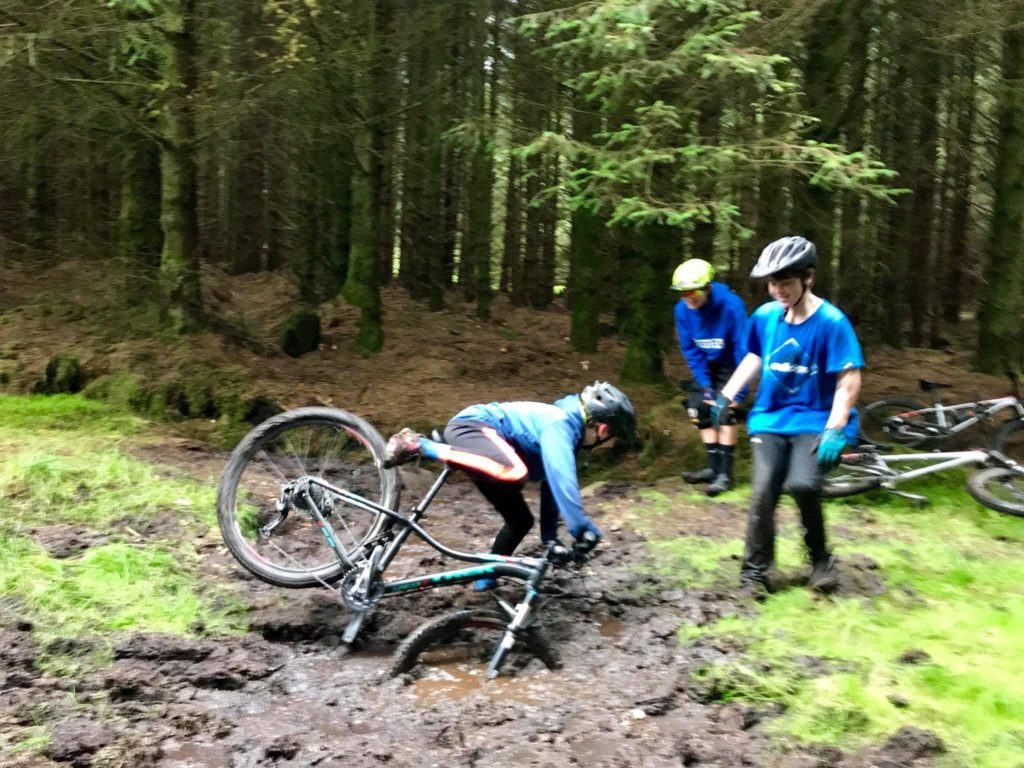 Enjoying the fruits of their labour, a brave cyclist attempts an impossible manoeuvre in thick mud.