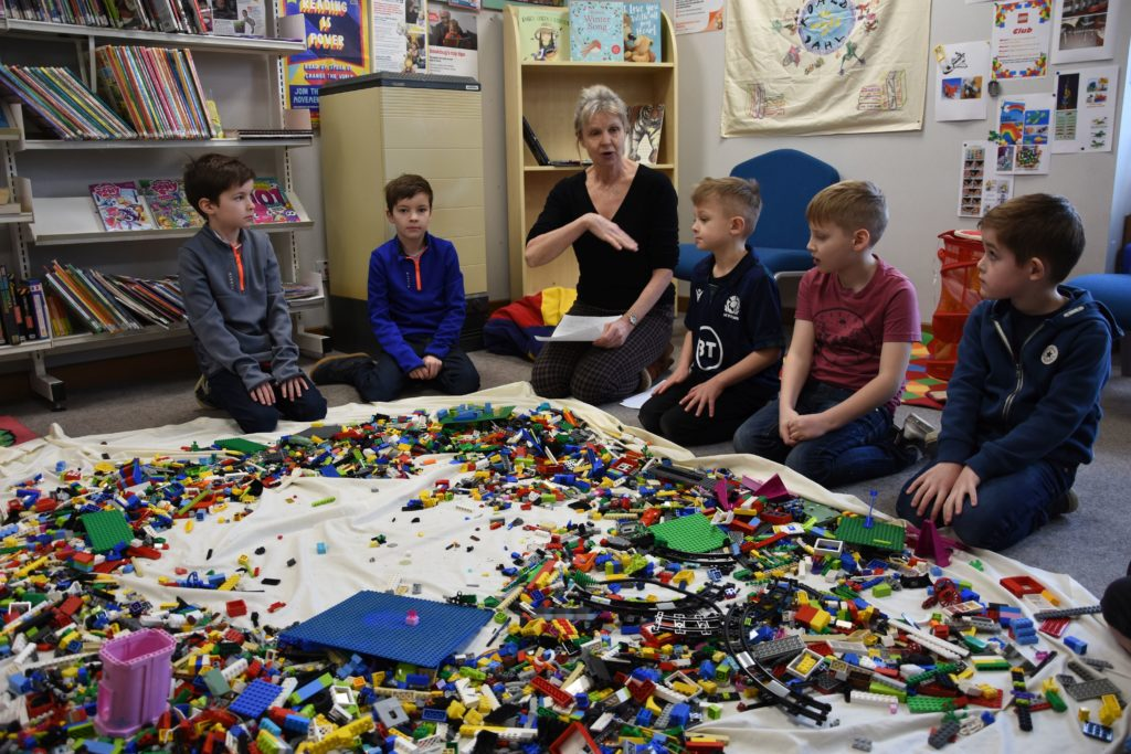 Librarian Jane Greenstreet encourages the children to think creatively when playing 'Cram it in' where participants compete to hold the highest number of blocks in one hand.