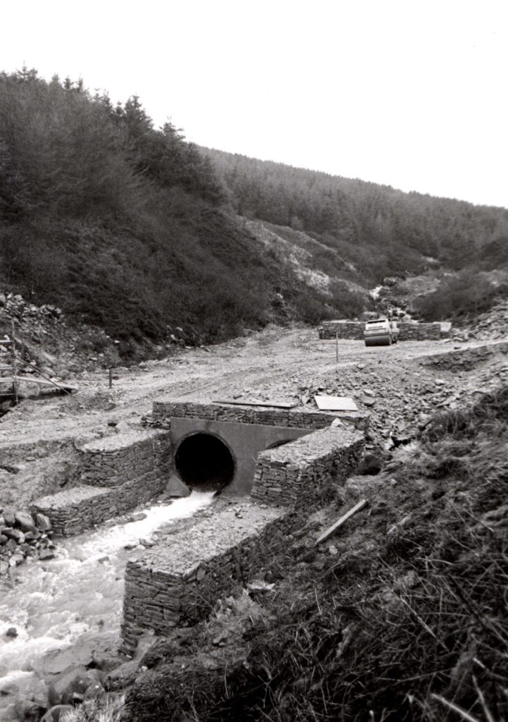 Work continues on the Iron Bridge on the Ross Road and this picture shows the extent of the task and how the river has been channelled into two huge pipes with stones and gabions around them.