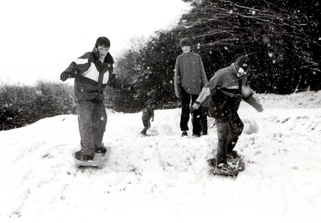 Robbie MacDonald and Donald Robertson turn their sledges into snowboards at Ormidale Park as Simon Ross Gill awaits his turn.