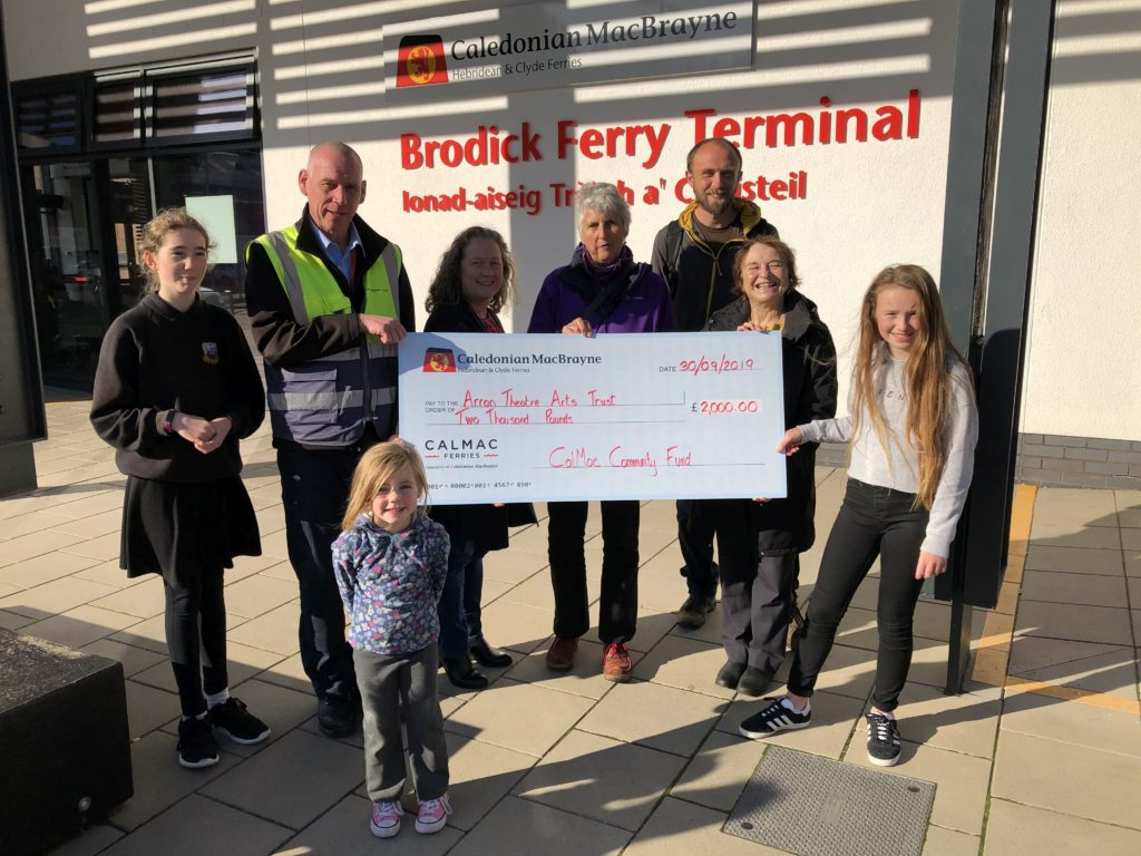 A CalMac representative presents the Arran Theatre and Arts Trust with a donation for the Wee Mac Book Festival.