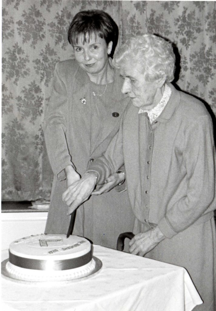 President Alice Anderson helps Betty Currie cut the cake at the 80th anniversary. At the time Betty had been a member of Shiskine WRI for 69 years and had rarely missed a meeting.