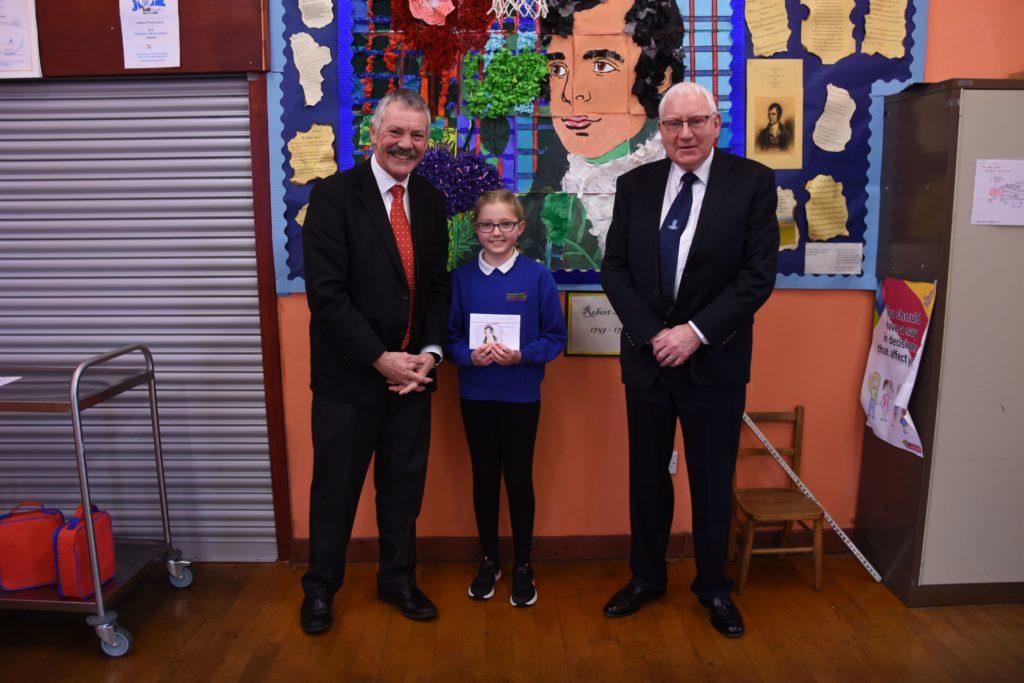 Lamlash Burns Club president Douglas Auld and secretary Andrew Martin pictured with Shiskine winner Olivia McNeice.