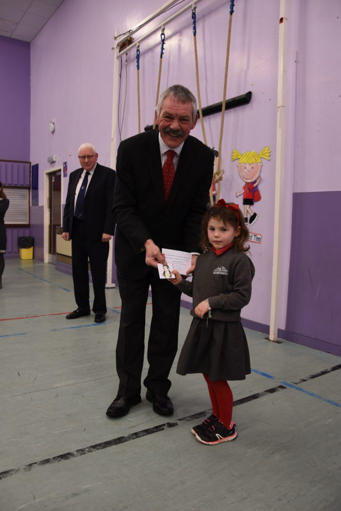 P1 pupil Bonnie Atkinson receives her commemorative medal from Burns Club president Douglas Auld.