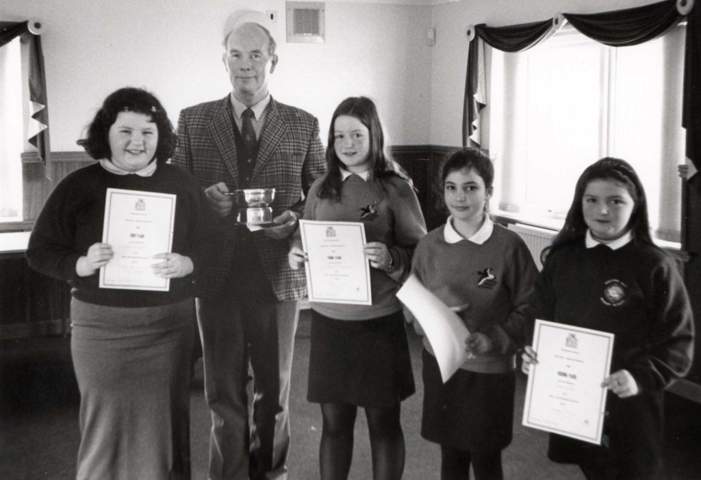 Stewart Lambie presents the winners of the Burns Speaking competition with their certificates and prizes. P5-7 winners were June Bunyan, Seonaid Anderson, Sabrina Beaton and Kirsty McBain.
