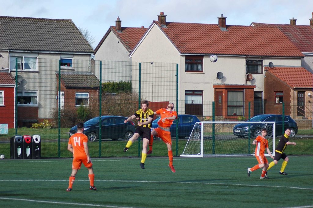 Leaping high into the air Arran's Matthew Dobson and a Kilbirnie player tussle for the ball.