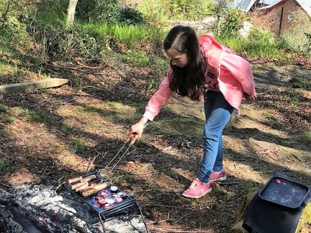 A Brodick primary youngster learns how to cook on a barbeque.