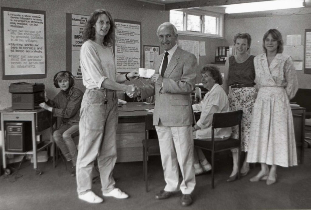 The Talking Banner became a registered charity in 1990 after being set up under the CODA umbrella. Here Grace Kay, CODA's treasurer, hands over money already raised to Dick Cameron of the new charity.