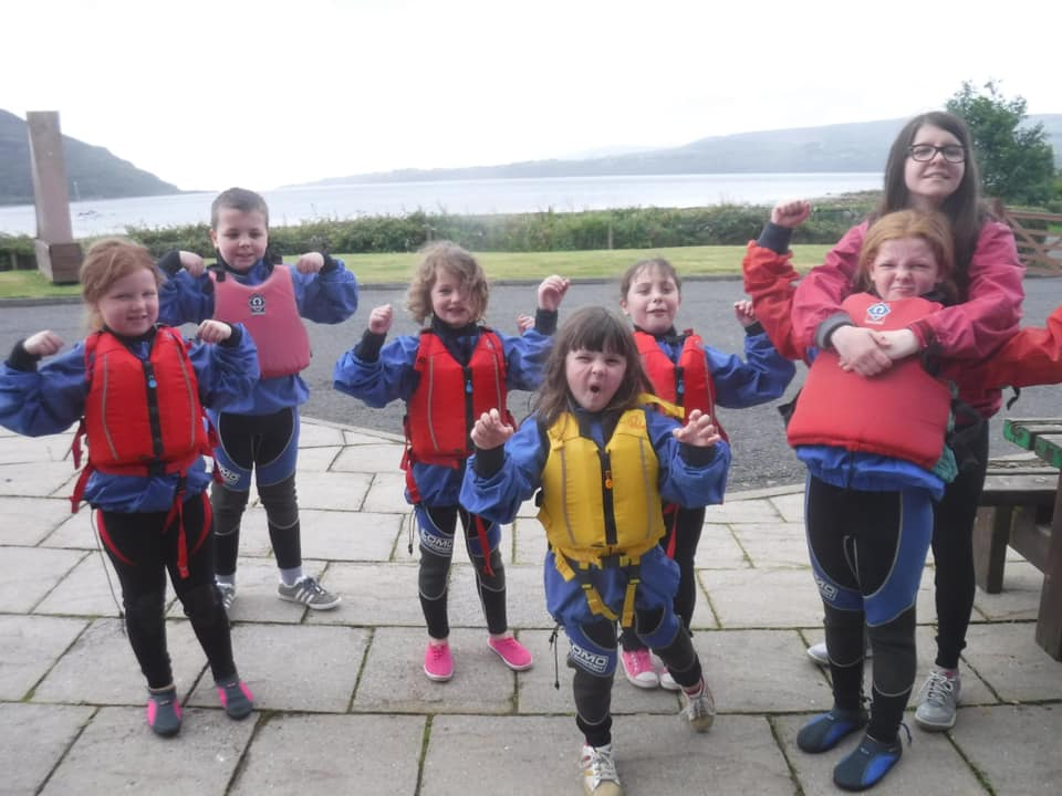 The children don lifejackets and psych themselves up to go kayaking.